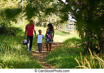Happy Black Family Walking In City Park With Picnic Basket