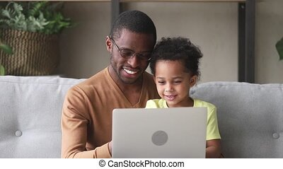Happy black father teach kid son to read use laptop