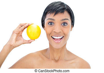 Happy black haired woman holding an orange