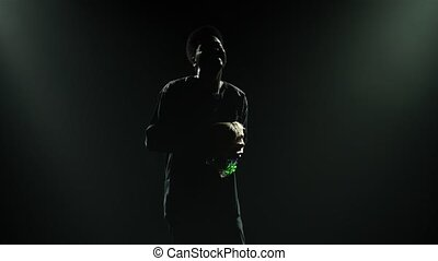 Happy black man enjoys playing an African rhythm instrument shekere that makes rattling sound. Bright instrument beads glisten in studio light against a black background. African folklore