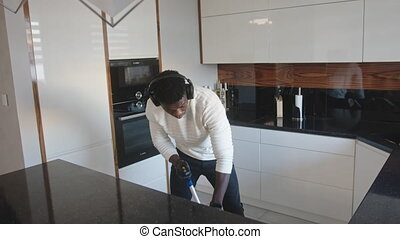 Happy black man listening music on headphones dancing and singing while cleaning floor in the kitchen. High quality 4k footage