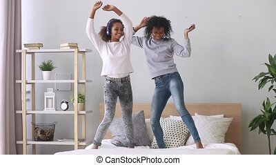 Happy black mom and daughter wearing headphones dancing on bed
