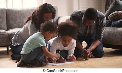 Happy black mom dad and kids drawing together at home
