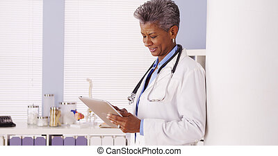 Happy Black Senior doctor standing in office with tablet