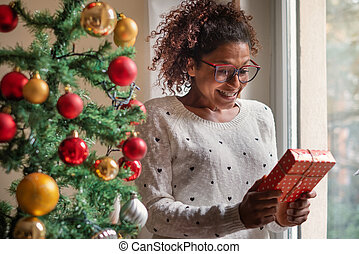 Happy black woman opening christmas presents at home