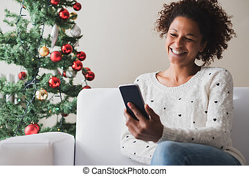 Happy black woman reading message during christmas celebration days