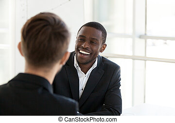 Happy black worker smiling having talk with colleague