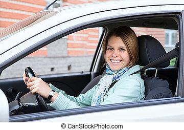 Happy blobd woman holding steering wheel in new car