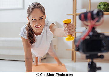 Happy blogger holding a hand weight while smiling to the camera