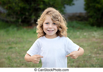 Happy blond child indicating himself an loughing in a park