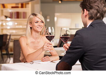 Happy blond girl in love with nice man. Drinking wine in...