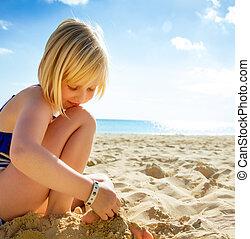 happy blond girl in swimwear on beach playing
