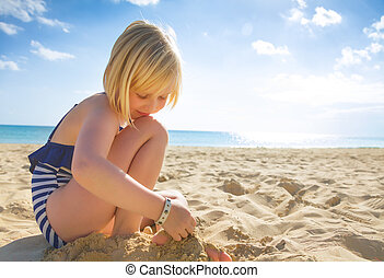 happy blond girl in swimwear on beach playing