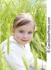happy blond little girl sit on green spikes meadow