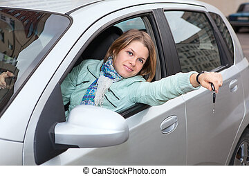Happy blond with car key showing in window