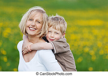 happy blond woman carrying her son