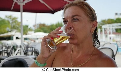 Happy blond woman drinking fresh beer on a sea beach in slow motion