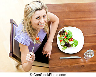 Happy blond woman  holding a tomato