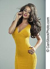 Happy blond woman in yellow dress in studio