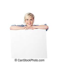 Happy Blond Woman Leaning On White Sign