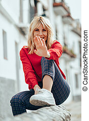 Happy blond woman sitting outdoors putting her hand near the camera.