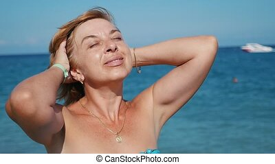 Happy blond woman smiling and putting her hair in order on a sea beach in slo-mo