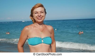 Happy blond woman standing and smiling on a sea resort in summer in slo-mo
