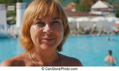 Happy blond woman standing and smiling on sea resort with blue waters in slo-mo