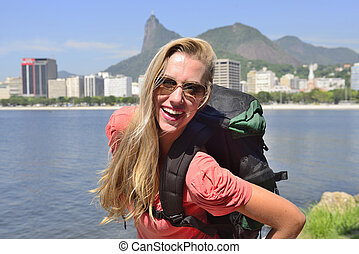 Happy blond young backpacker woman traveling at Rio de Janeiro with the Christ Redeemer in background.