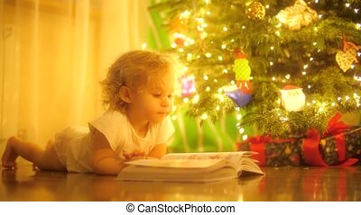 Happy blonde baby girl looks at pictures in a fairytale book...