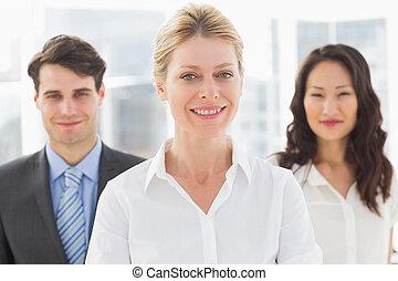 Happy blonde businesswoman in front of her team