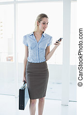Happy blonde businesswoman using her smartphone holding a briefcase standing in her office
