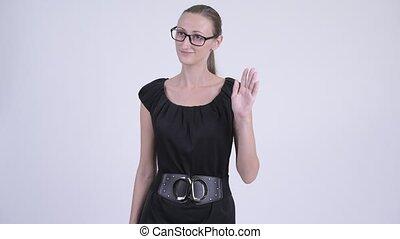 Happy blonde businesswoman with eyeglasses waving hand -...