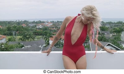 Happy blonde dressed in red swimsuit stands on the open balcony overlooking Bali