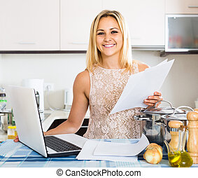 female signing documents at the kitchen