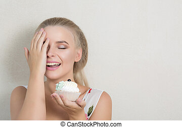 Happy blonde girl covers her face by hand and holding sweet cream dessert. Space for text