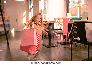 Happy blonde girl running with shopping bags