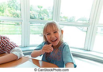 Happy blonde girl sitting at the table