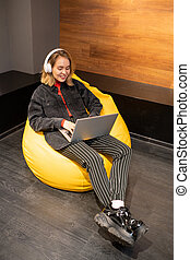 Happy blonde girl sitting in soft comfy yellow leather armchair and relaxing