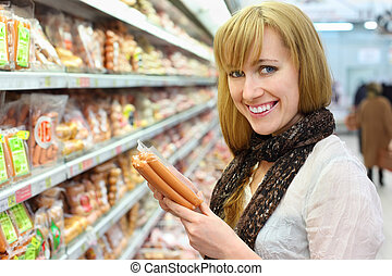 Happy blonde girl wearing white shirt chooses sausage in large store; shallow depth of field