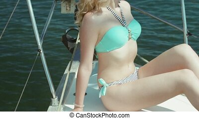 Happy blonde in bikini having fun on yacht