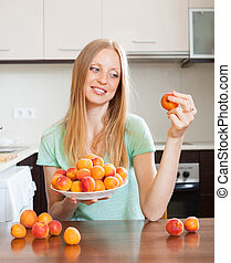 blonde long-haired woman eating apricots in home kitchen