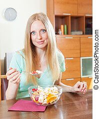 Happy blonde long-haired woman eating fruit salad with yoghurt