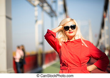 Happy blonde model posing in red cloak, wears sunglasses on a blurred city background