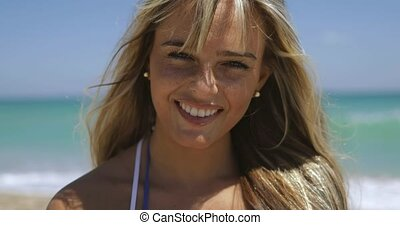Happy blonde on beach in sunshine - Content smiling woman...
