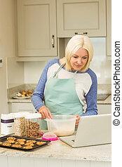 Happy blonde preparing dough following online recipe