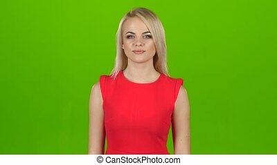 Happy blonde shows gesture all right, thumbs up. Green screen