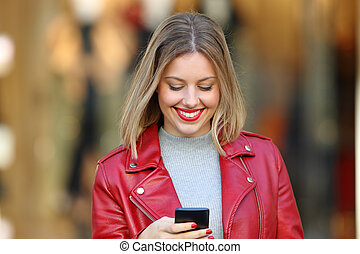 Happy blonde using a smart phone in a mall