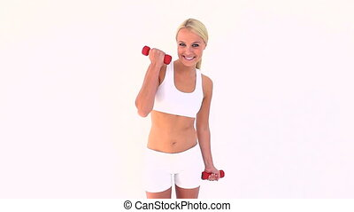 Happy blonde using dumbbells