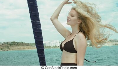 Happy blonde with long hair posing while standing on yacht in bikini